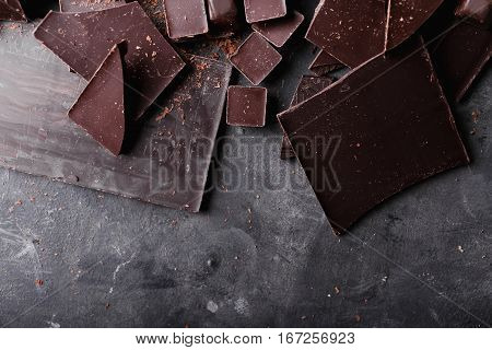 Chocolate chunks. Chocolate bar pieces. A large bar of chocolate on gray abstract background. Chocolate candies. Background with chocolate. Slices of chocolate. Sweet food photo concept. Copyspace