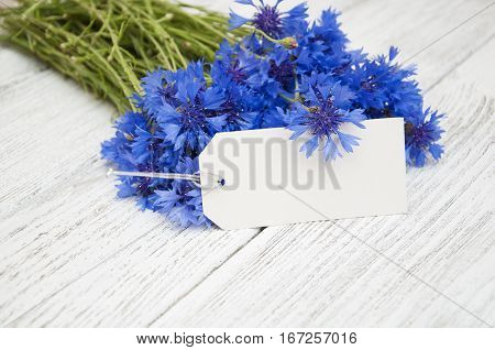 Bouquet of cornflowers with gift card on a wooden background