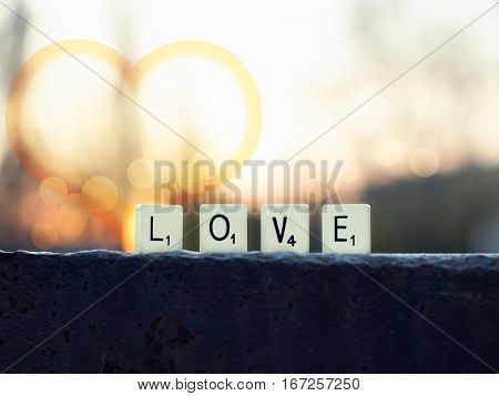 scrabble word love at sunset and bokeh lights