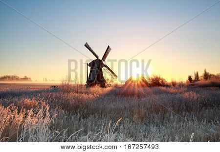 beautiful sunrise behind windmill in winter Holland