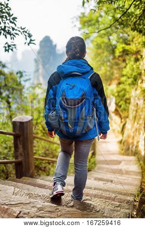 Young Female Tourist With Blue Backpack Descending Stairs