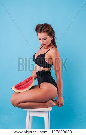 Picture of young woman holding a big slice watermelon in the studio
