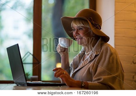 Elderly woman with laptop. Senior lady holding white cup. Fresh news and hot coffee.