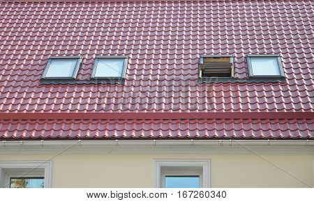 Red Metal tiled Roof with New Dormers Roof Windows Skylights Rain Gutter System and Roof Protection from Snow Board