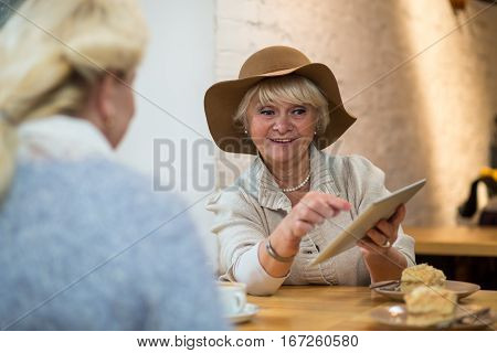 Senior female with a tablet. Smiling lady at cafe table. New os works much better.