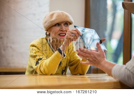 Old lady holding a tablet. Senior woman at the table. New design and improved hardware.