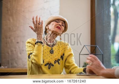 Arrogant senior woman. Old lady at the table. Pride and hypocrisy.