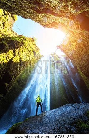 Man in the cave near the Gljufrabui waterfall, Iceland, Europe