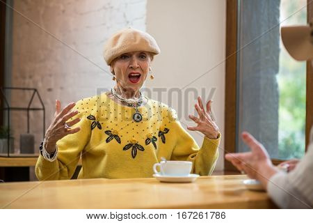 Surprised senior woman indoor. Lady at table in cafe. The unbelievable story.