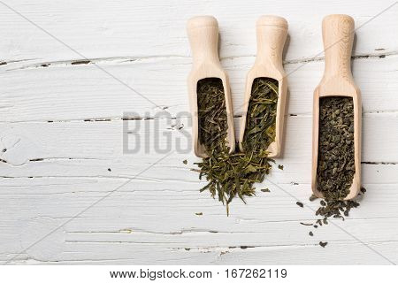 Green tea leaves bancha sencha gunpowder in scoop on white wooden background with copy-space. poster