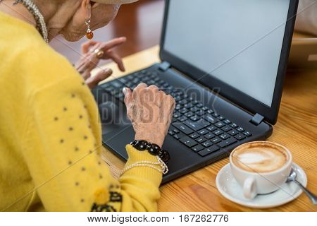 Senior female with laptop. Cup of coffee on saucer. Getting familiar with new technologies.