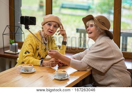 Elderly women taking selfie. Two senior ladies in cafe. Testing new monopod.