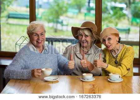 Elderly ladies showing thumbs up. Three women drinking coffee. Friends in great mood.