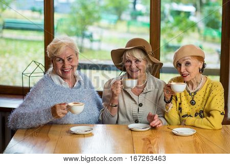 Women with coffee smiling. Three happy senior ladies. Old friends meet in cafe.