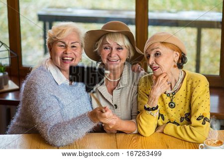Three women with selfie stick. Smiling senior ladies in cafe. Years pass but friendship remains.