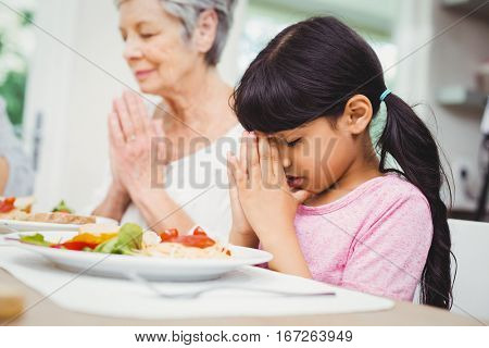 Granny and granddaughter praying at dining table in home