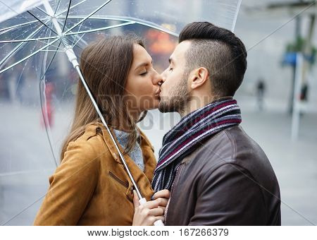 Beautiful young couple having tender moments on a rainy day standing under a transparent umbrella wearing leather jackets in the city center - passionately couple kissing under the rain - Love concept