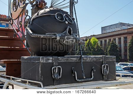 Funny outdoor metal sculpture in the form of a Bun and suitcase
