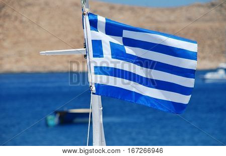 The Greek National flag flying in Emborio harbour on the Greek island of Halki.