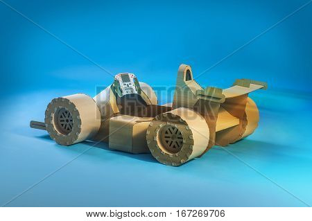 Photo of cardboard racing car on blue background