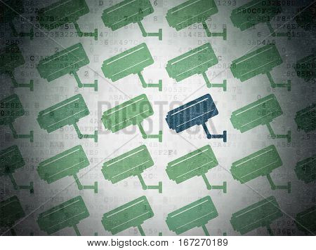 Safety concept: rows of Painted green cctv camera icons around blue cctv camera icon on Digital Data Paper background