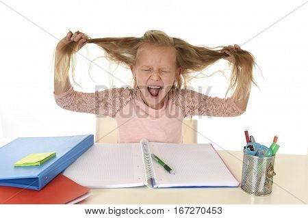 sweet young little schoolgirl pulling her hair desperate in stress while sitting on school desk doing homework tired and exhausted screaming crazy isolated on white background