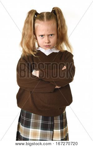 cute and sweet young schoolgirl in pigtails and school uniform looking angry and upset in frustrated and unhappy face expression in education and kid learning concept isolated white background