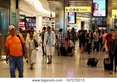 London, UK, 03 Jul. 2009: Passengers in Heathrow Airport. Toilet direction banner and various Ad banners.