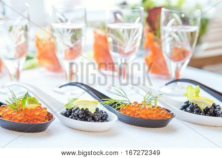 Red And Black Caviar Fish In White, Black Spoons