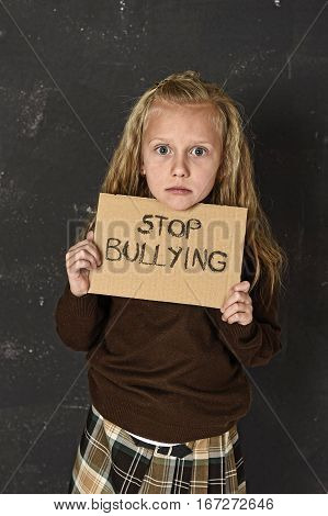 young little cute schoolgirl scared and sad asking for help showing message with stop bullying text written in stress in front of school blackboard in education and childhood problem concept