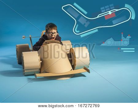 photo of young racer in glasses on a cardboard racing car on blue background
