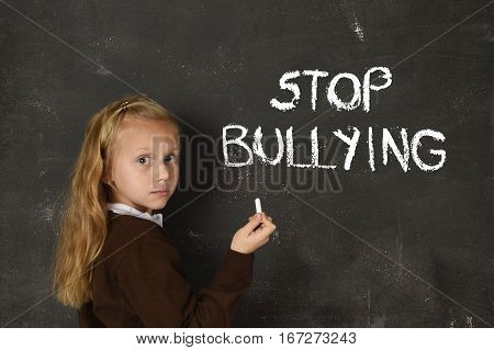 young little cute schoolgirl scared and sad writing the words stop bullying text written with chalk on school blackboard suffering stress in education and childhood problem concept