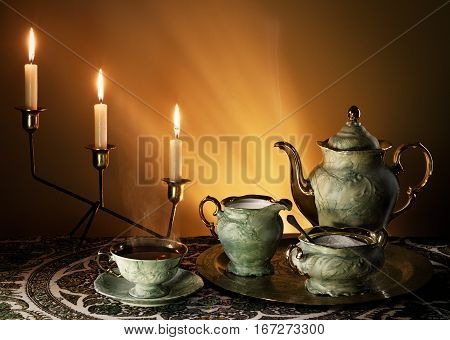 Tea Art Composition: Porcelain Sets Of Cups, Kettle, Along With Tea, Milk, Sugar, Candles. Smoke Ste
