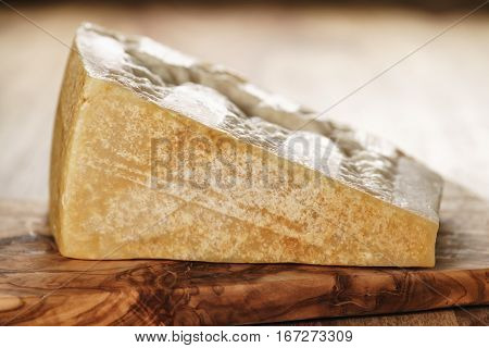 big chunk of italian parmesan cheese on wooden cutting board, simple rustic photo