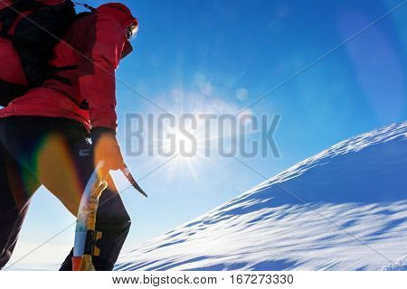 Concept: overcome challenges. Mountaineer faces a climb at the top of a snowy peak.