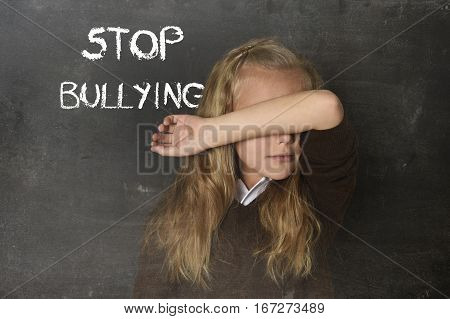 young little cute schoolgirl scared and sad covering her face and the words stop bullying text written with chalk on school blackboard suffering stress in education and childhood problem concept