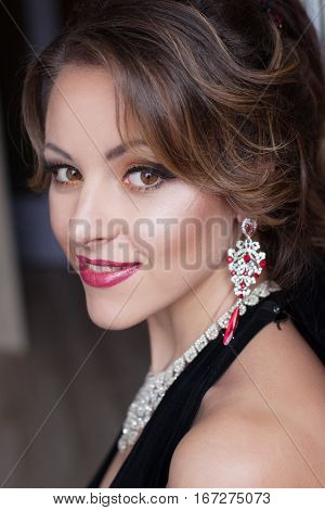 Portrait of a beautiful girl in a black evening gown with a jeweled