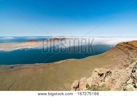 View on the volcanic coastline and Isla Graciosa from Mirador del Rio vista Lanzarote Spain