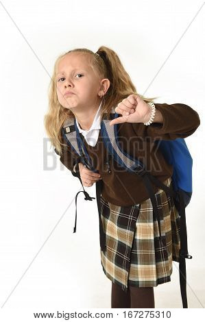 sweet beautiful little schoolgirl tired and exhausted carrying on her back heavy school backpack looking sad and depressed in weight of school books concept isolated on white