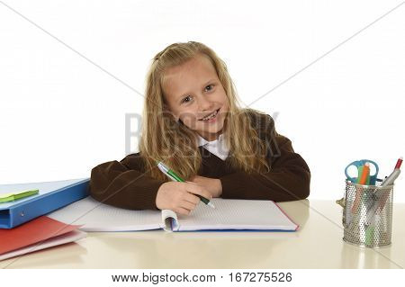 little beautiful schoolgirl in school uniform with blond hair smiling happy sitting on desk doing homework isolated on white background in success and child education concept
