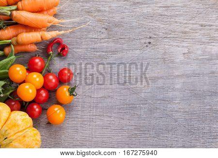 Autumn vegetables background: tomatoes carrots pumpkin runner beans chilies