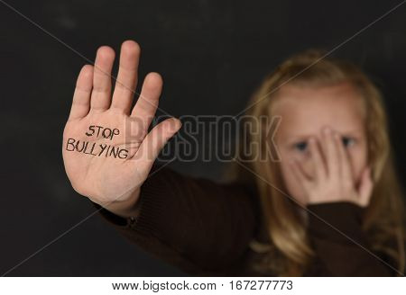 young little cute schoolgirl scared and sad asking for help showing hands with stop bullying text written on her palm in stress in front of school blackboard in education and childhood problem concept poster