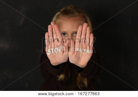 young little cute schoolgirl scared and sad asking for help showing hands with stop bullying text written on her palm in stress in front of school blackboard in education and childhood problem concept