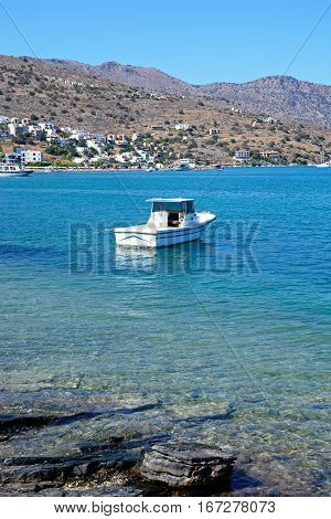 ELOUNDA, CRETE - SEPTEMBER 17, 2016 - Small boat moored in the bay with the coastline to the rear Elounda Crete Greece Europe, September 17, 2016.