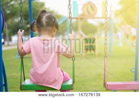 Children playing in Playground. Little girl having fun on a swing outdoor. Little girl is swinging at play ground when sun is setting.
