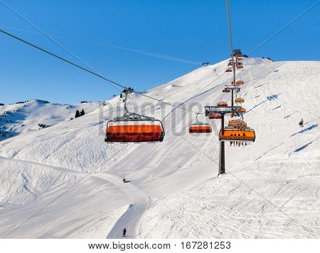 Chair ski lift with orange bubble shelter on sunny winter day. White snow and clear blue sky in Saalbach Hinterglemm Leogang Resort, Austria, Alps, Europe.