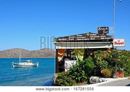 ELOUNDA, CRETE - SEPTEMBER 17, 2016 - Greek taverna along the waterfront with a boat moored in the bay Elounda Crete Greece Europe, September 17, 2016.