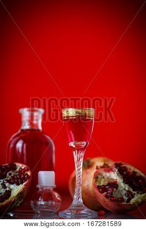 sweet pomegranate alcoholic cordial in the decanter with a glass on a red background