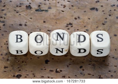 Bonds Text On A Wooden Cubes On A Brown Cork Background