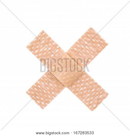 Cross shaped adhesive bandage sticking plaster isolated over the white background
